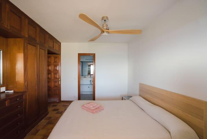 Habitación 1 con cama de 160cm de ancho, baño privado y ducha XXL, armarios empotrados, ventilador de techo y vistas al jardín y al mar.