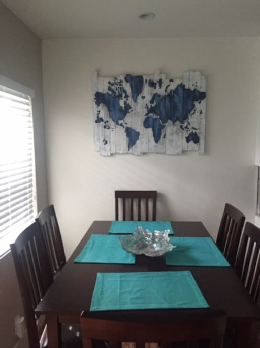 The kitchen table is spacious and ready for you to enjoy your morning coffee on.
