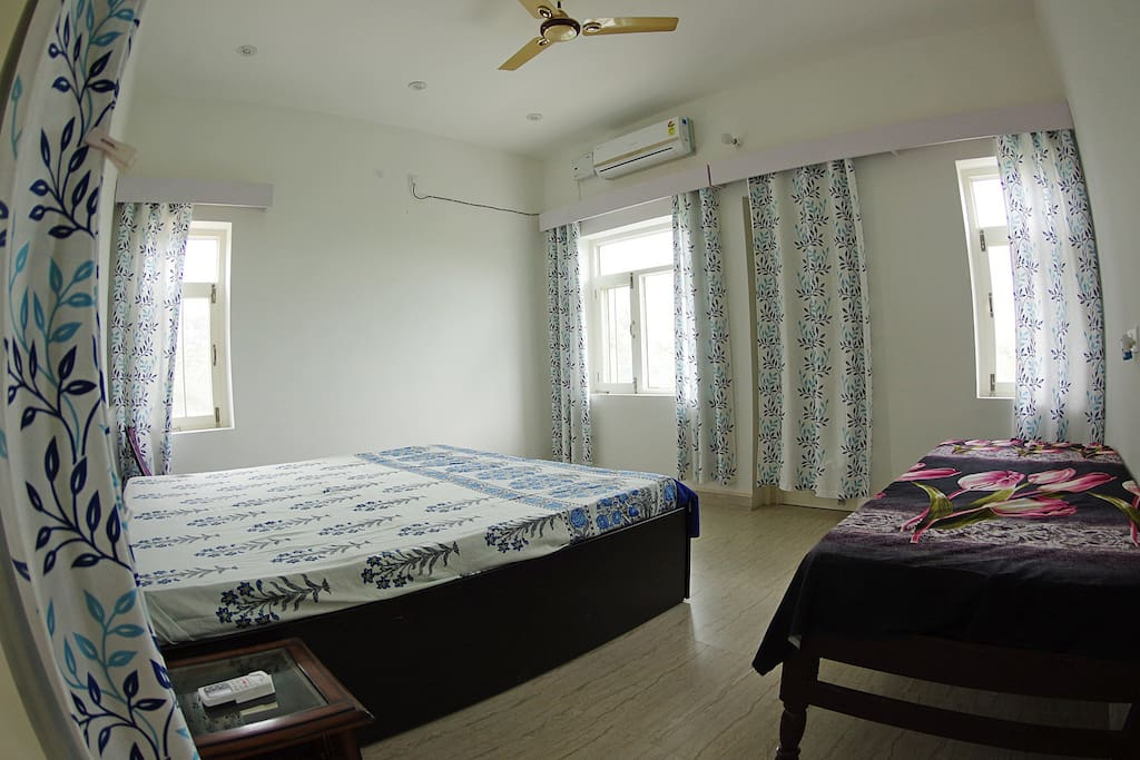 Spacious bedroom with Godrej Interio twin bed which is 6 1/2 ft long and features a Godrej Interio orthopedic mattress. You can see Pong reservoir from the windows. A patio outside lets you observe birds from close quarters.