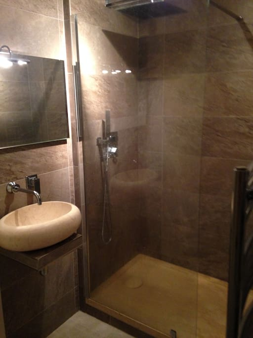Salle de bains carrelés, marbre et ciel de pluie