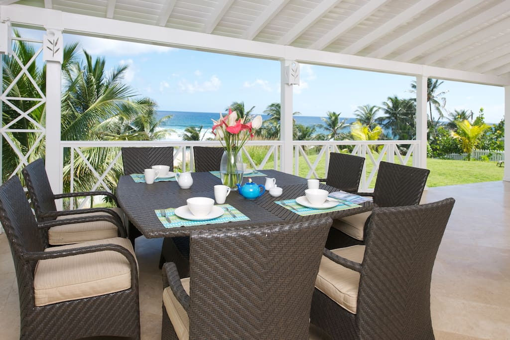 Dining table on wrap around veranda showing view of the sea.