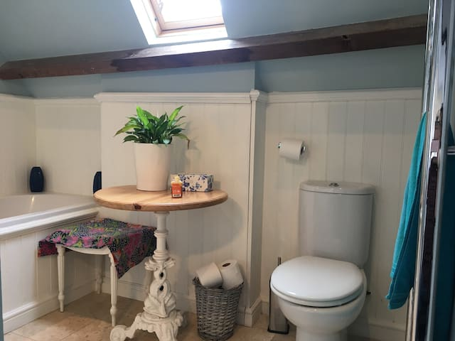 Attractive ensuite bathroom  with bath, electric shower and toilet.
