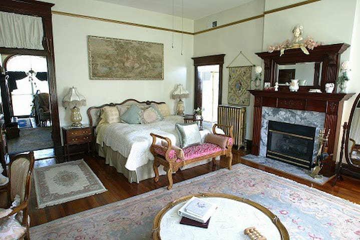 king bed, tapestry in gilded frame, fireplace with wood mantle and marble surround, coffee table with marble inset top, oriental rug