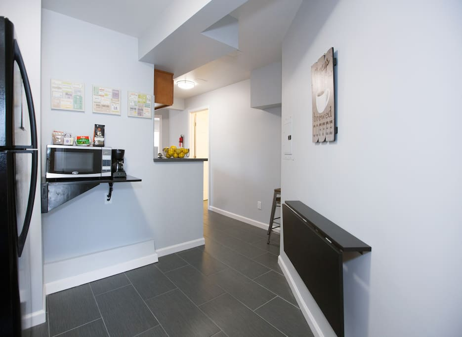 Entry into the apartment is spacious & features a wall mounted table for a quick bite or to send a few emails.  Coffee station  stocked with all you need!