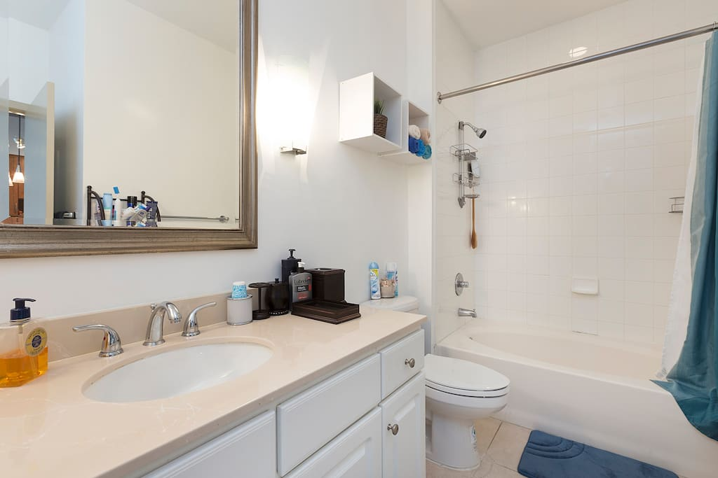 Large bathroom is super clean. All the counter space is for you. Hair dryer, iron, ironing board, towels, toiletries provided.