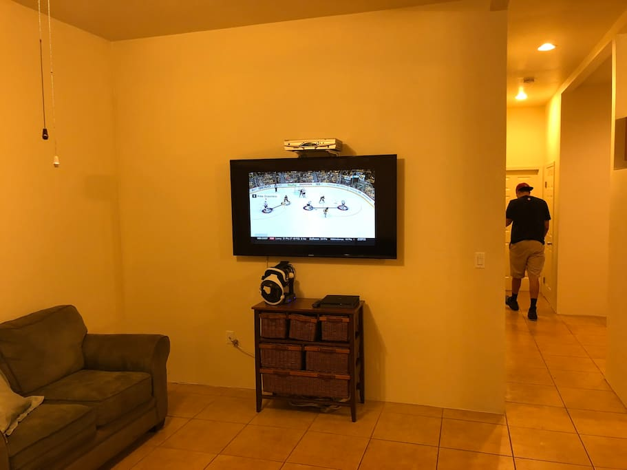 """Living room with 60"""" HDTV, cable box with remote, PS4 Pro and VR Bundle."""