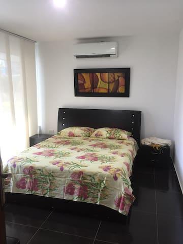 Habitación principal con cama doble y sofá cama, baño interno.