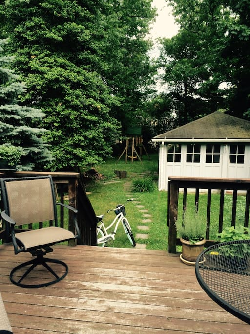 Deck and back yard which has a swing set and zipline