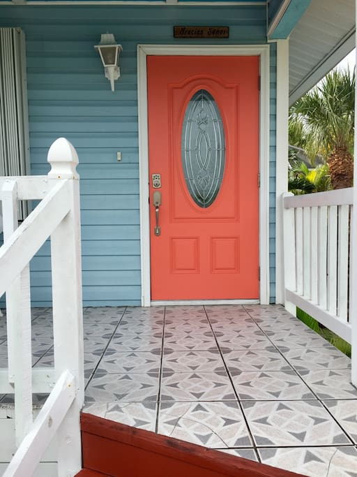 A coral colored door welcomes you