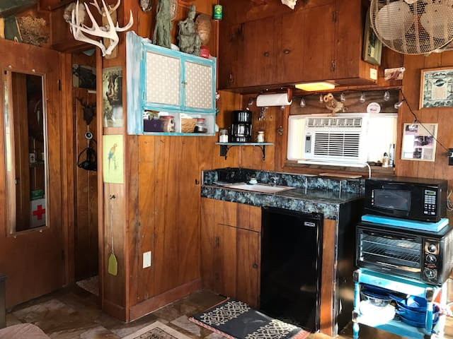 Kitchen area: cold water sink, pantry stocked with essentials (plates, bowls, silverware, coffee cups, salt/pepper, tea, sugar, creamer, Keurig coffee maker,  coffee pods , napkins and paper towels, Microwave, large toaster oven, two burner stove top, pots, and pans.