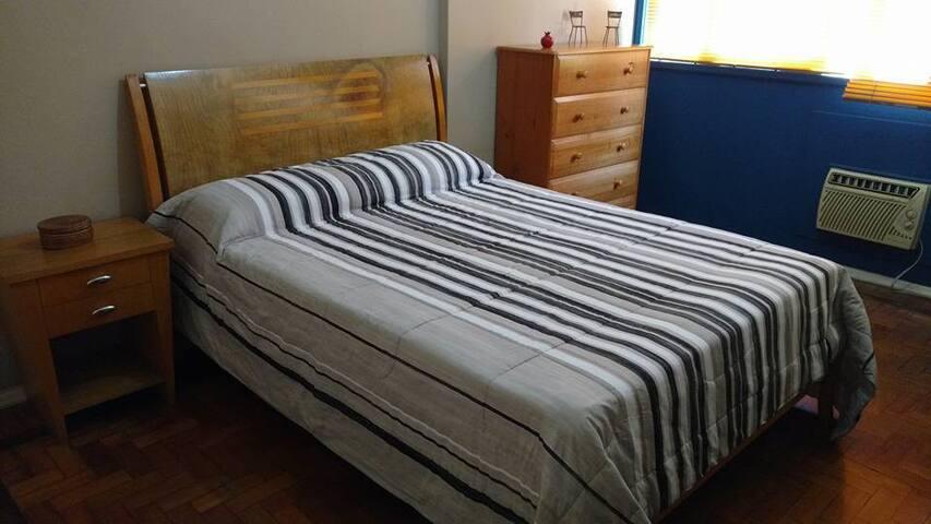 Quarto 2 com cama de casal, comoda, mesas laterais, ar condicionado e ventilador de teto