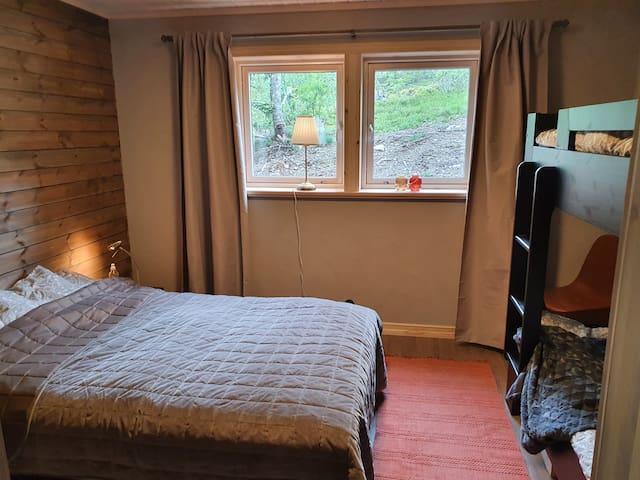 Sovrum med dubbelsäng samt våningssäng