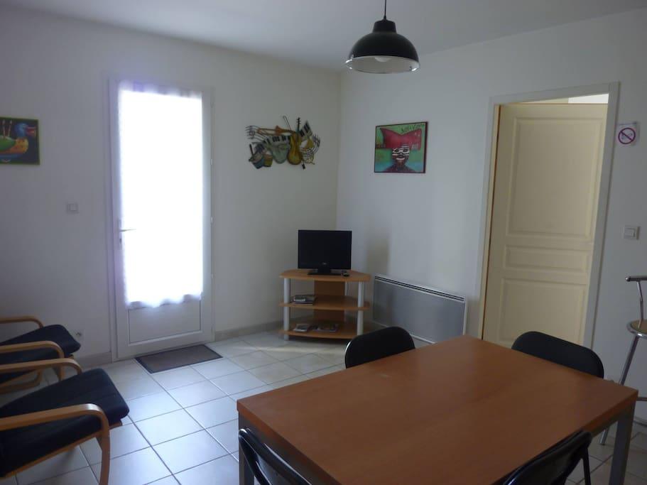 Salon et coin cuisine avec accès à une chambre de chaque côté