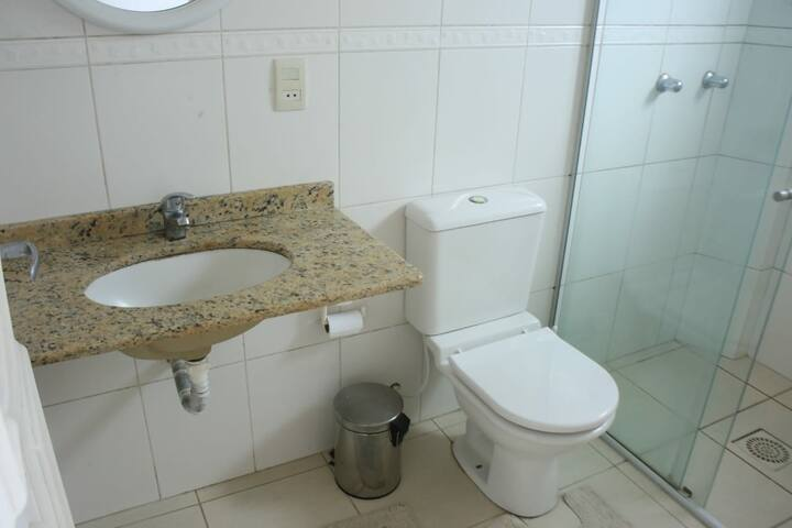 Banheiro da suíte, com box de vidro e pia em mármore.