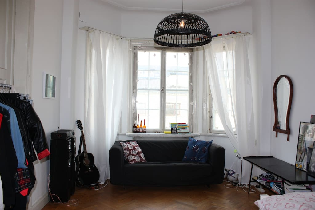 Big window, sofa and a hanger for clothes.