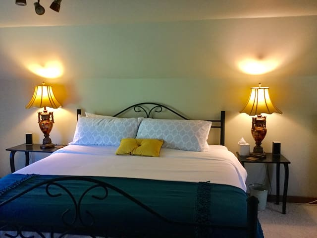 Your upstairs bedroom is welcoming, and cleanly cozy with a oversized chair, and king size bed