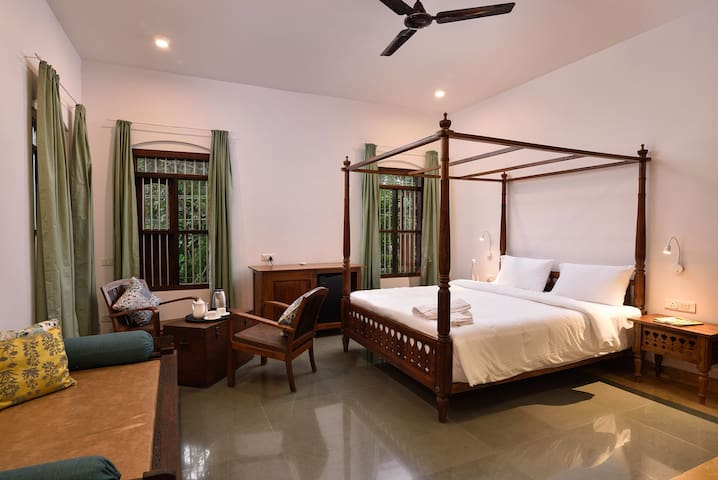 Bedroom of the villa with colonial bed and two chairs setup