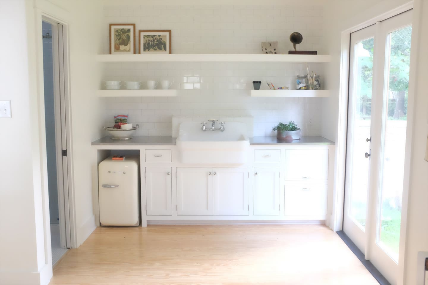 -kitchenette-  farmhouse sink with disposal, mini fridge, french press, electric kettle, and microwave