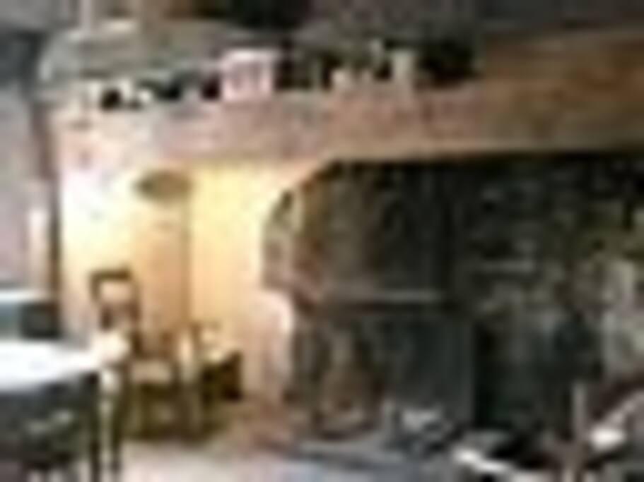 Grande cheminée ancienne du séjour typique avec bois fourni