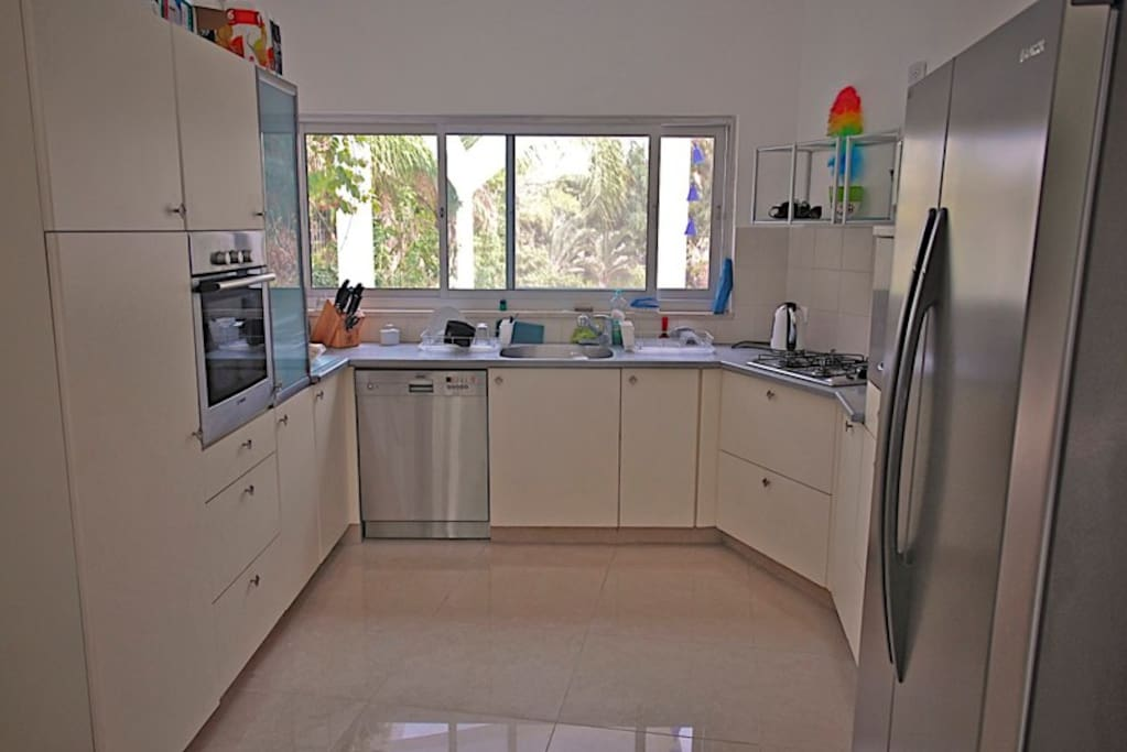 Fully equipped kitchen with modern appliances (Fridge, stove, oven, dish washer, coffee machine, kettle, and toaster)