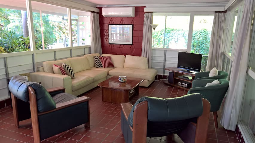 The lounge/living area is fully air-conditioned and contains a large leather sofa, arm chairs, coffee table, flat screen TV and DVD.  The room's louvre windows capture the breeze and overlook the patio and tropical garden.