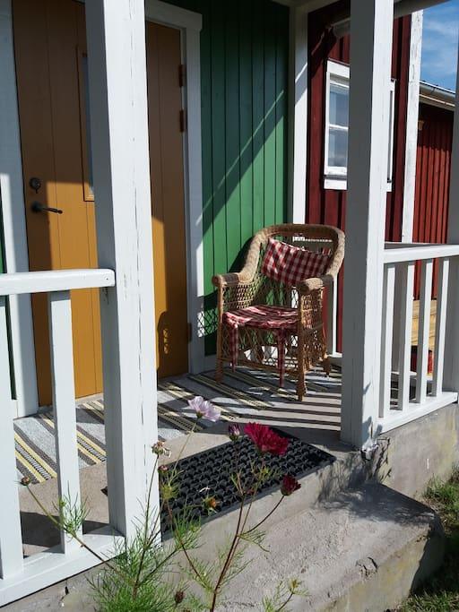 Ockragul dörr, kromoxidgrön verandavägg.
