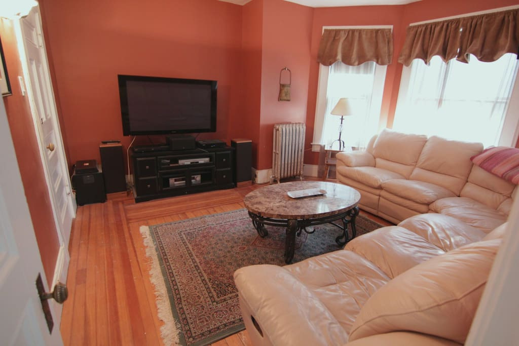 Leather L shaped couch with plasma TV.
