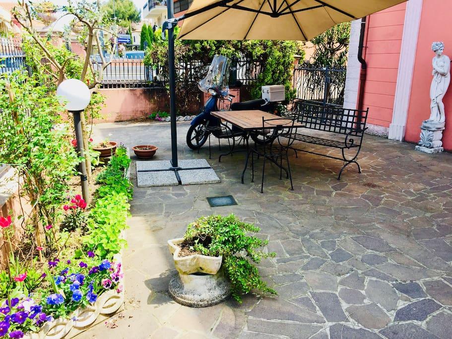 Giardino di ingresso con tavolo e ombrellone per pranzi o cene all'aperto