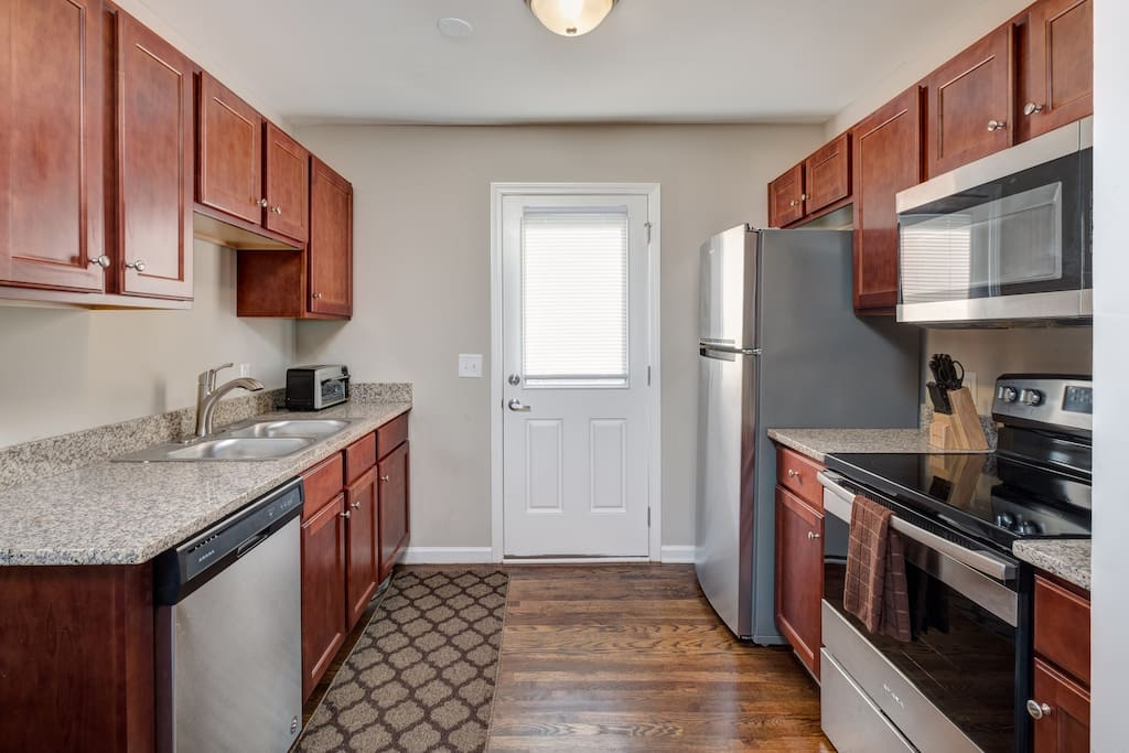 The well-equipped kitchen in Unit 1 includes upgraded stainless steel appliances and access to the shared patio.