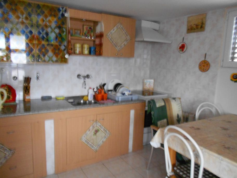 Kitchen. There is an electric stove, a 2-chamber refrigerator, a necessary set of dishes, a dining table.