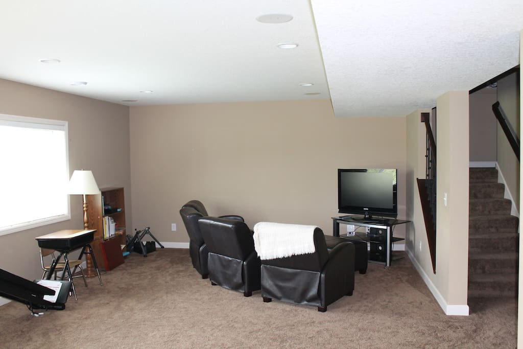 Basement entertainment area with television, seating for four, and exercise equipment