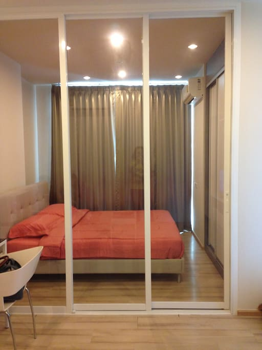 The bedroom is separated from the living room already have bed cover, air conditioner, wardrobe, and dressing table.