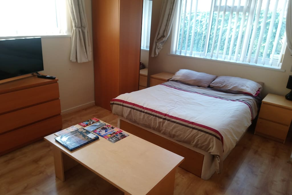 A spacious double bed room with two chests of drawers, a sofa, coffee table, wardrobe with full length mirror and smart TV.