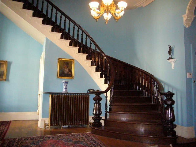 Mahogany staircase spirals down to greet you in the foyer.