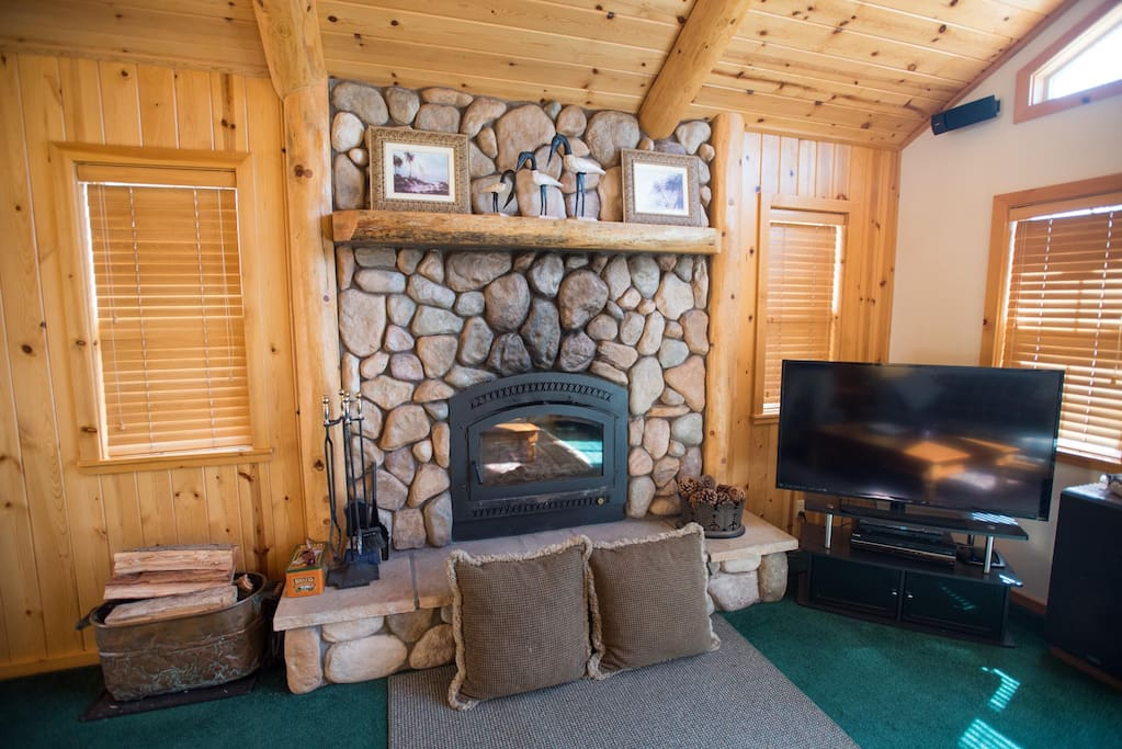 Stone fireplace in the living room with large screen TV