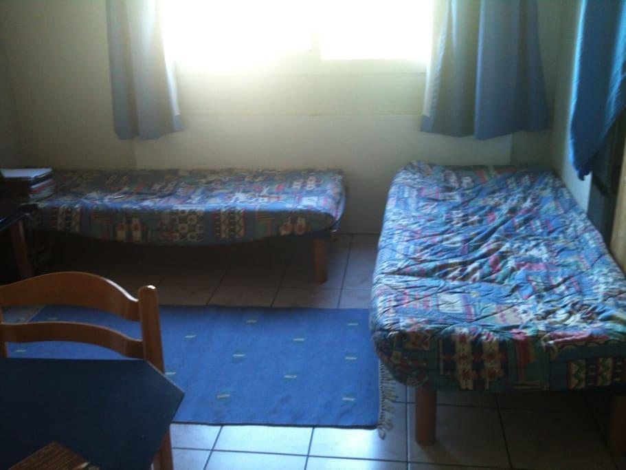 La Pièce principale, très lumineuse, avec deux lits simples, une grande table pour 6 personnes, et le coin cuisine.