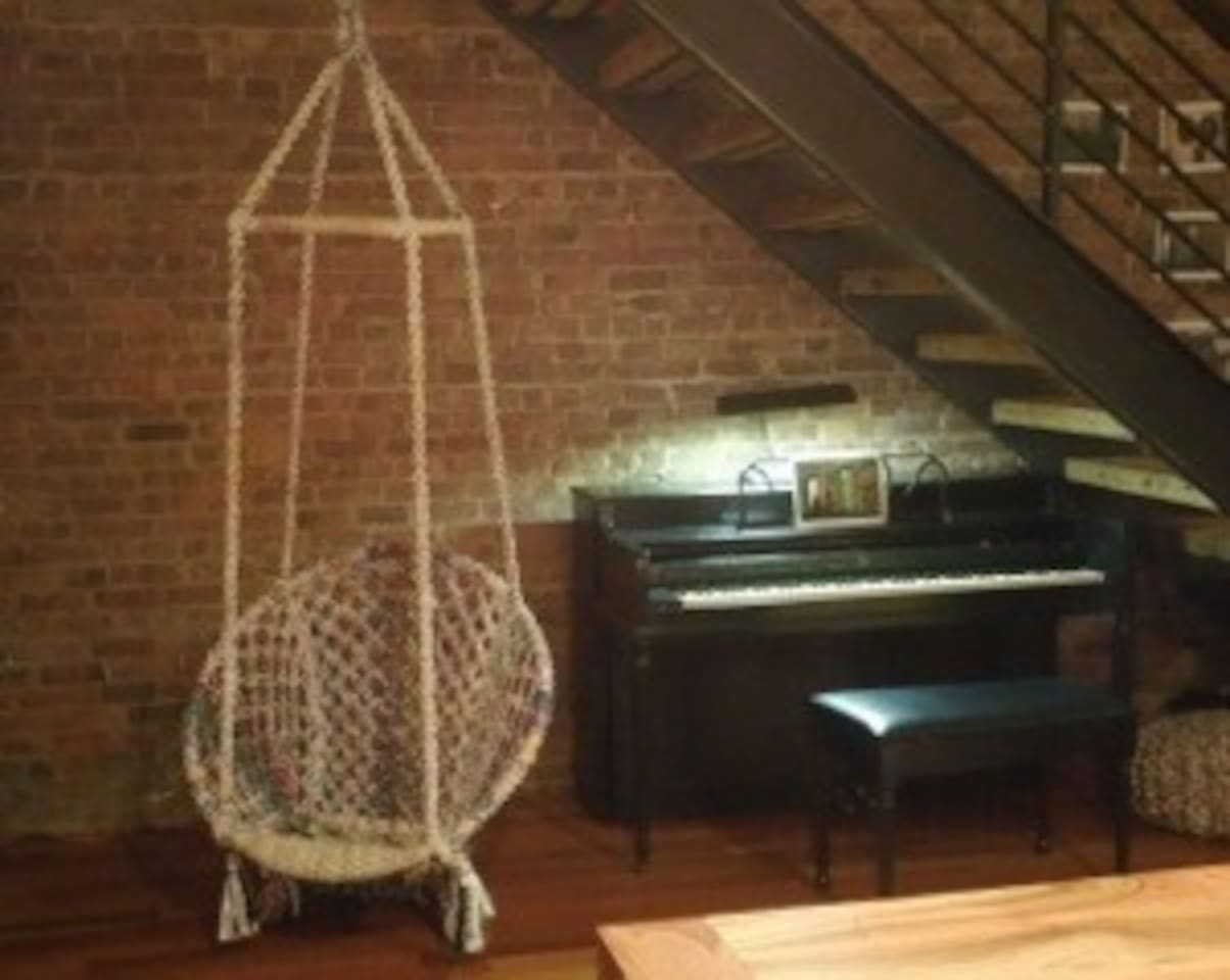Piano and suspended chair under custom steel staircase with hemlock treads