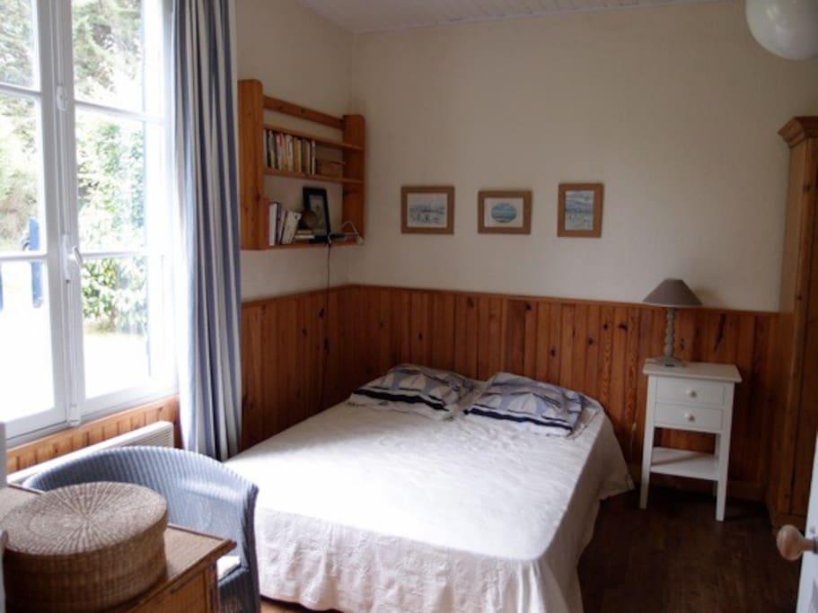 Chambre avec un lit double et des lits gigogne et un lit tiroir.