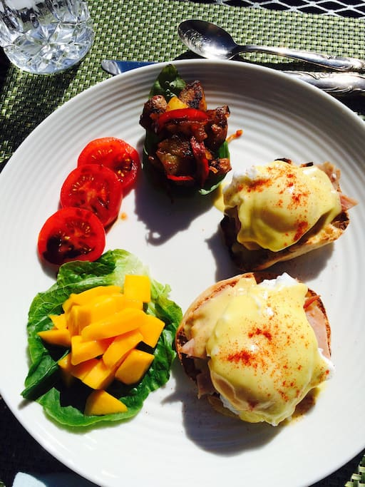 Eggs Benedict with oven roasted potatoes and peppers, Apple balsamic drizzled over Roma tomato and  a side of fresh mangos