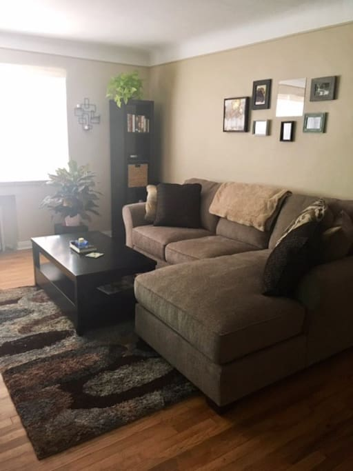 Living room with a spacious sectional couch, TV, and view of downtown Denver!