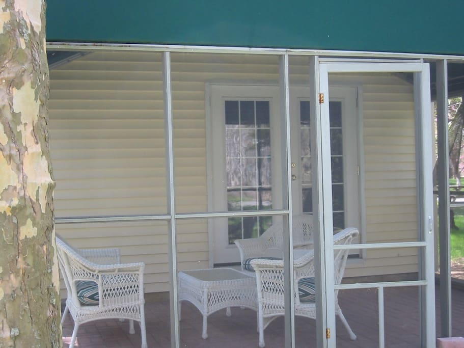 Cottage screened patio with awning, wicker furniture and light for evening use