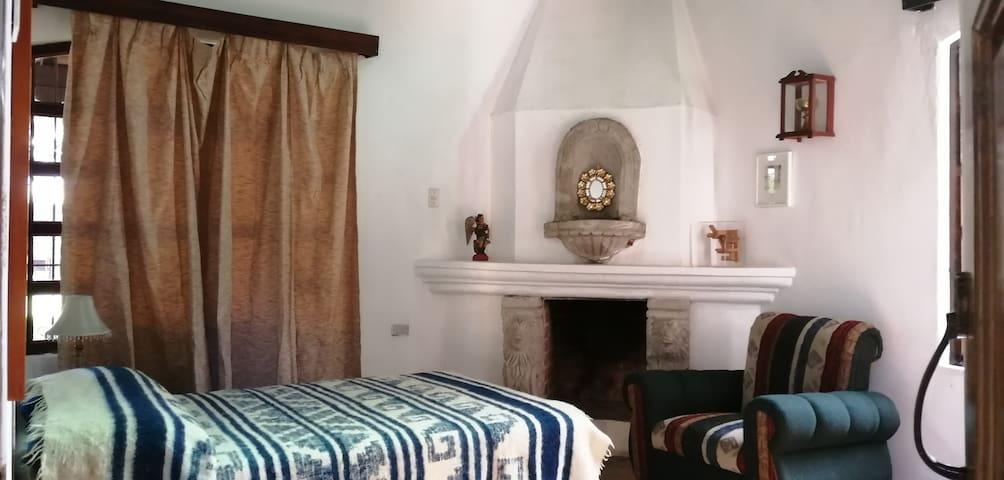 Habitación Individual con una cama matrimonial, baño privado, chimenea, TV, sofá.  Ideal para 1 o 2 personas.