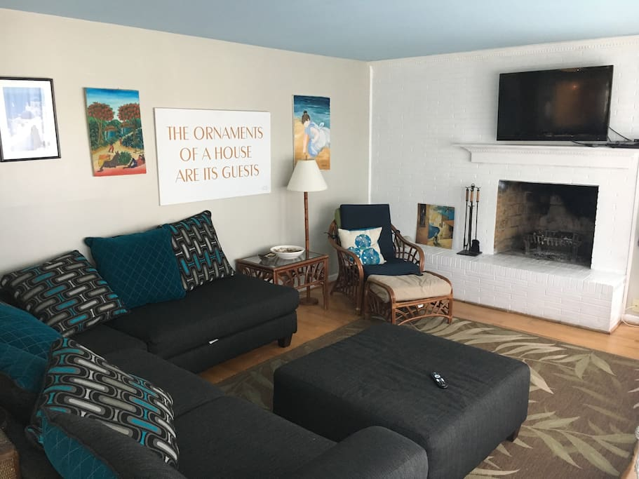 Freshly painted living room with large L couch, TV, working fireplace and wall of windows overlooking deck across sunny southern side of house.