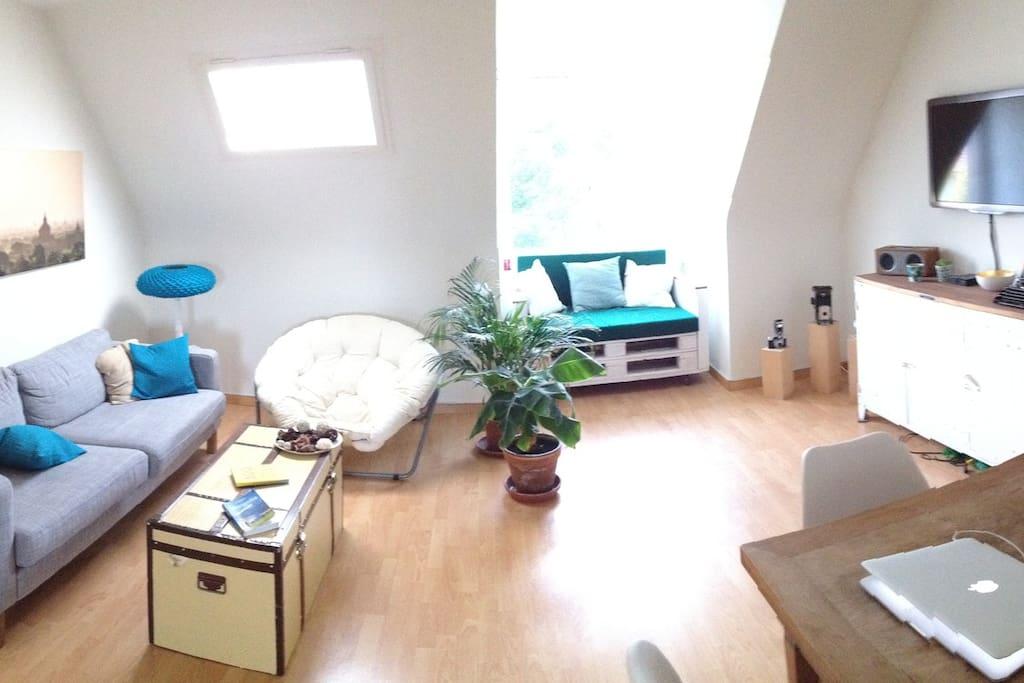 Das Wohnzimmer mit Esstisch, Musikanlage, Fernseher und gemütlichen Sofas