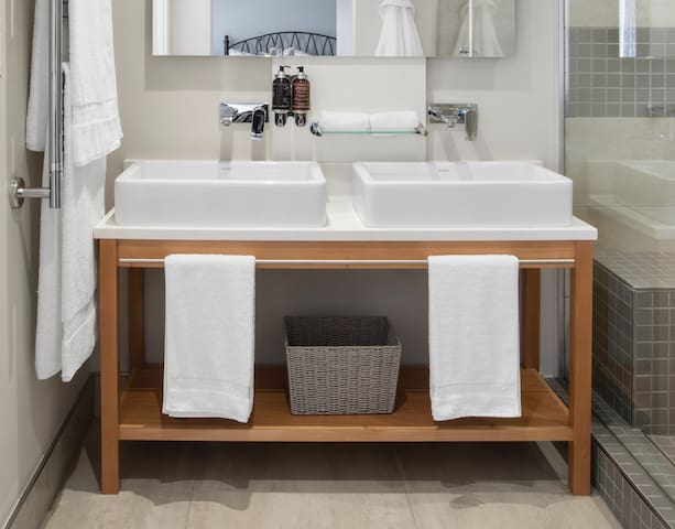 The modern bathroom has a large shower with built-in seat, high-end modern finishes, luxury amenities & towels.