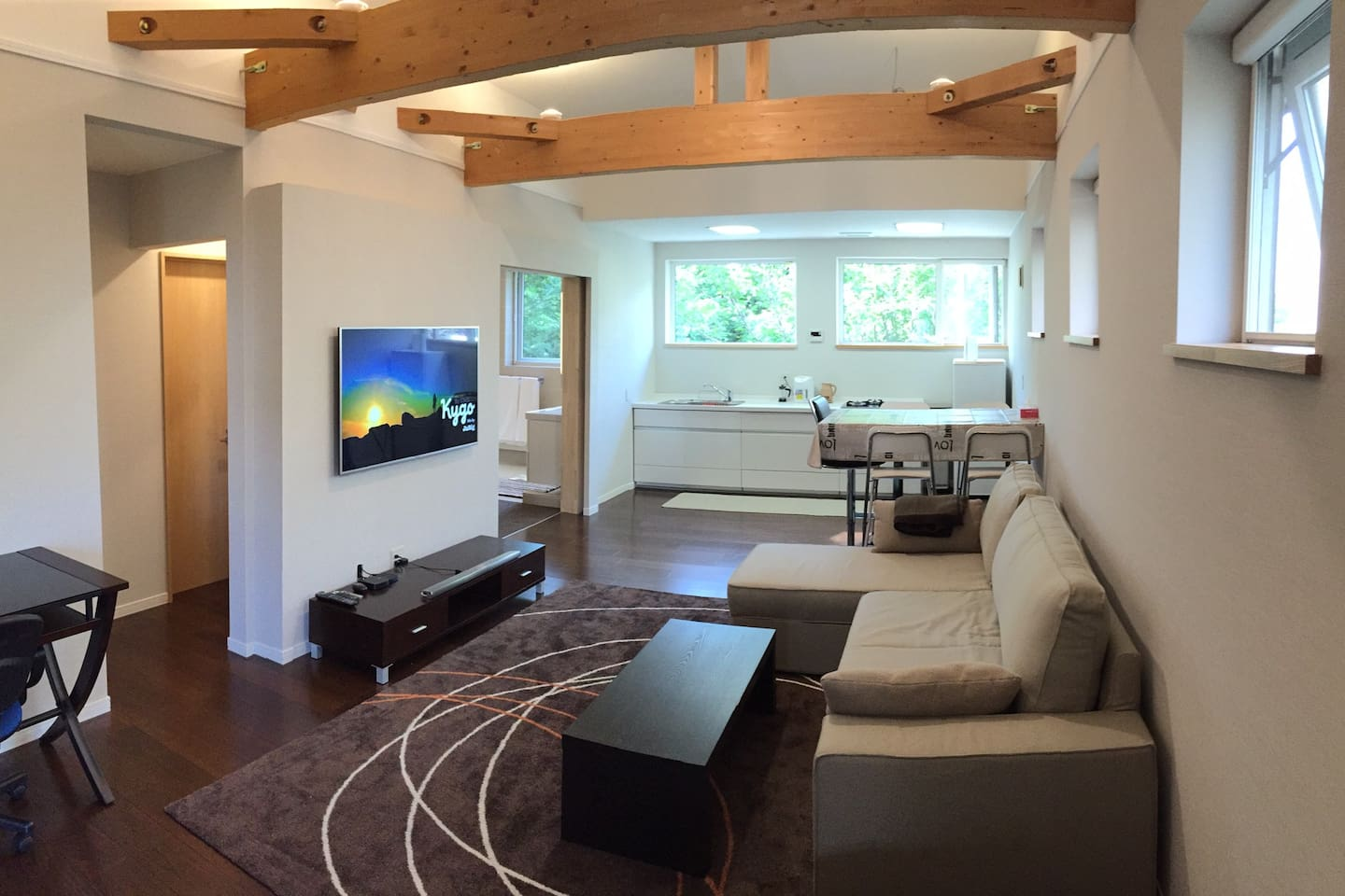 View from entrance looking toward lounge, dining area and kitchen. Sofa folds out to full sized queen bed. Bedroom entrance at far left hand side.