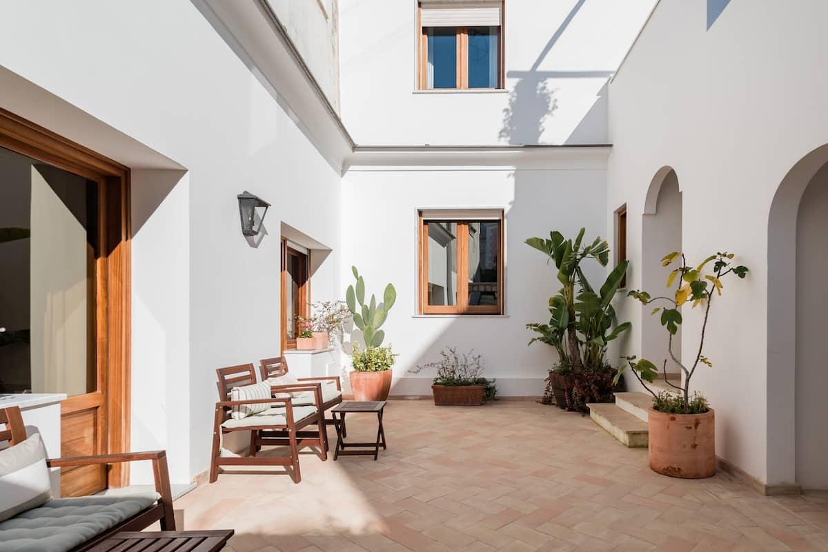 Camera in stile caprese con lussureggiante giardino mediterraneo