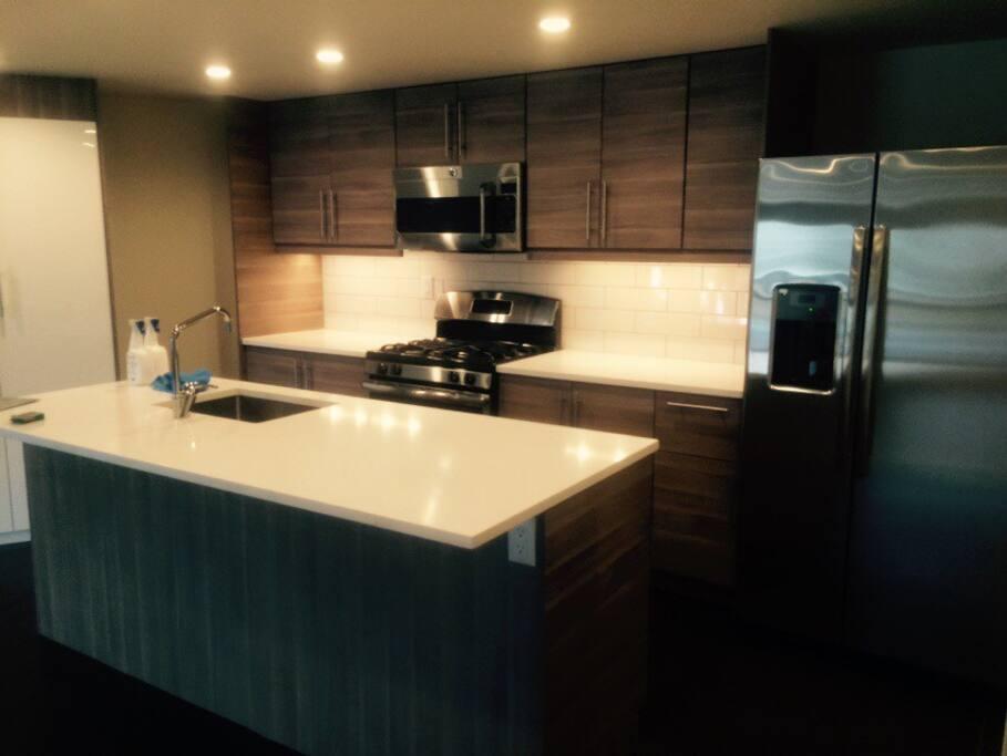 Kitchen - gas range/oven, sink and dishwasher in island.