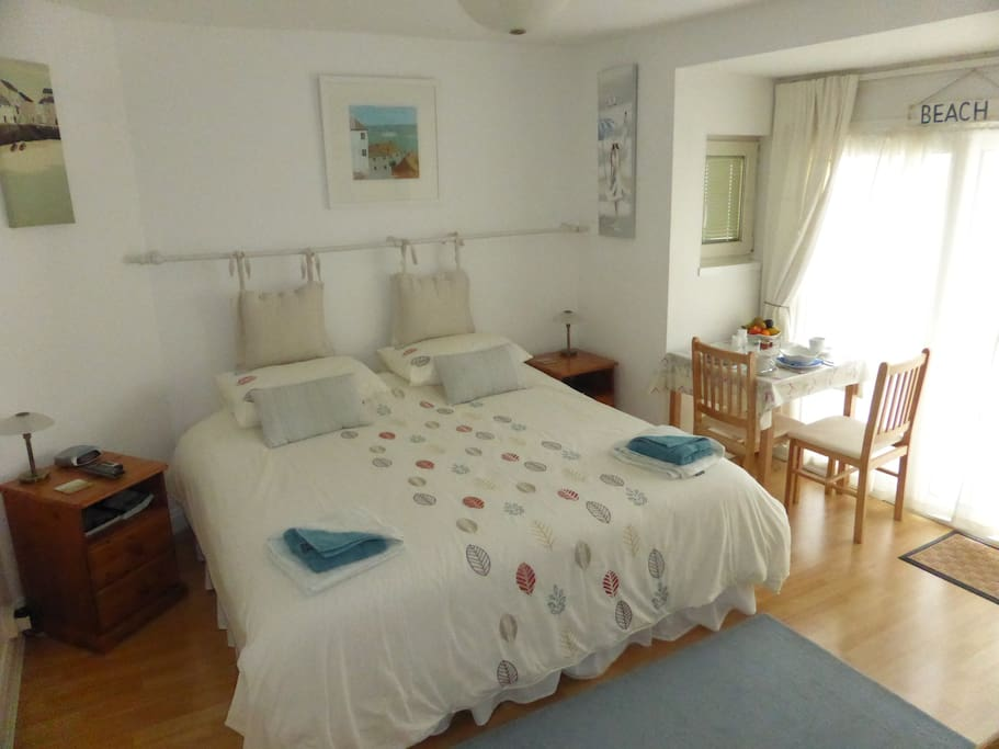 Super-king room, with your breakfast table laid and patio doors onto the decking.