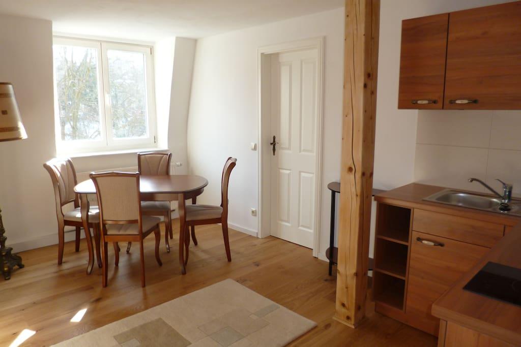 Wohnzimmer mit Schlafcouch und Küchenzeile